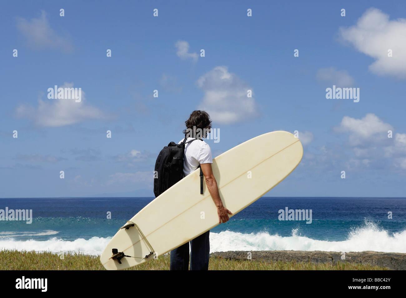 man holding surf board, facing sea - Stock Image