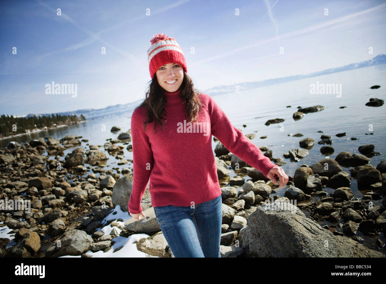 Woman walking on rocks near snowy lake - Stock Image