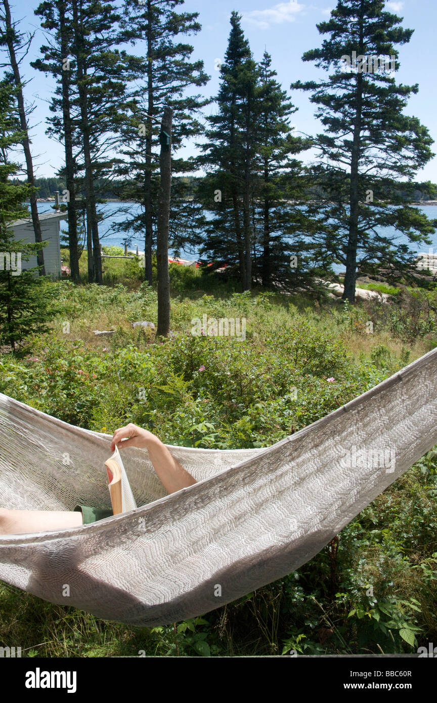 Woman relaxing on hammock and reading - Stock Image