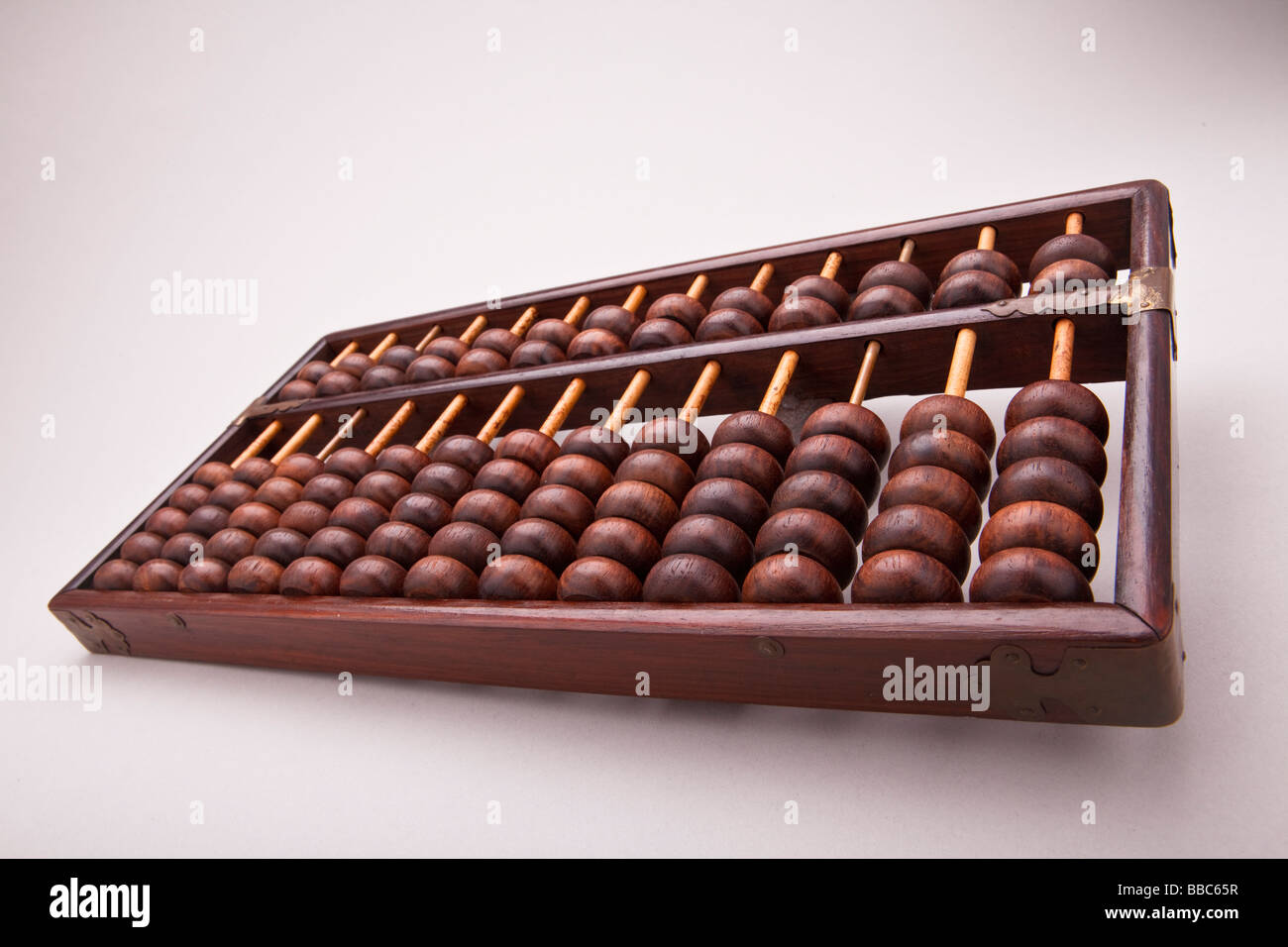 Large Chinese abacus on white background with studio lighting. - Stock Image