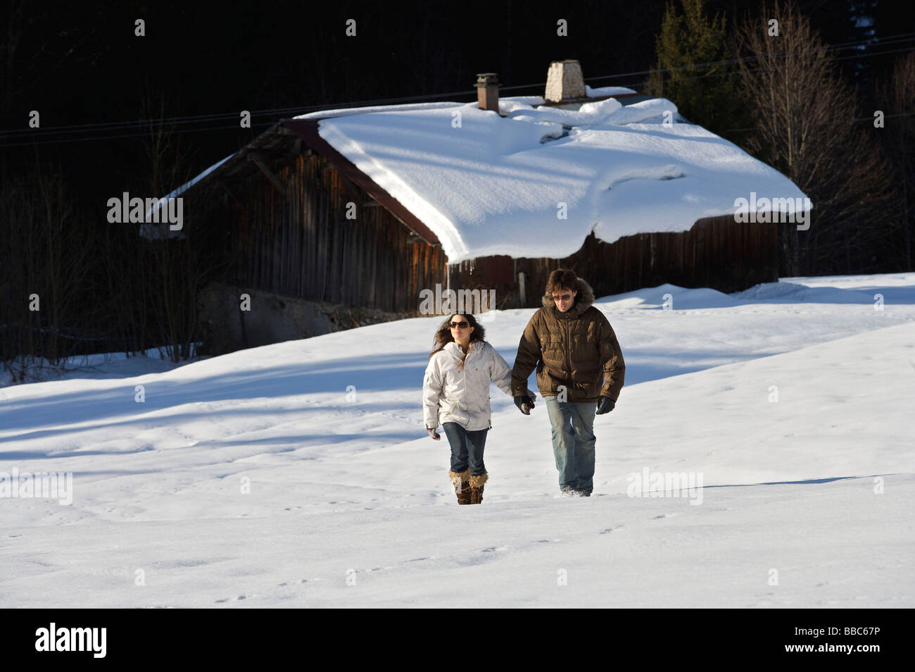 Couple walking in the snow. - Stock Image