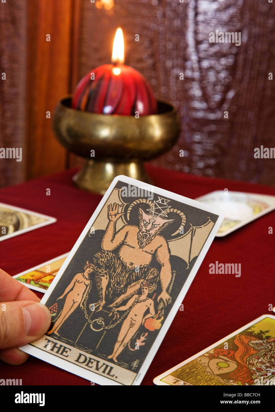 Tarot card spread with the reader holding the Devil from the Stock
