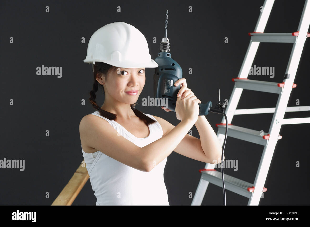 Young woman wearing hard hat, holding drill - Stock Image