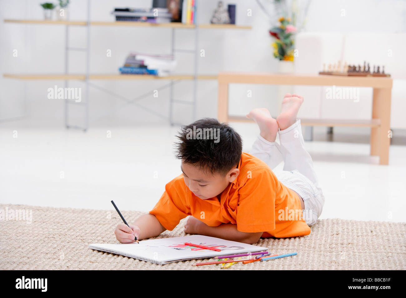 Boy lying on floor with sketch pad