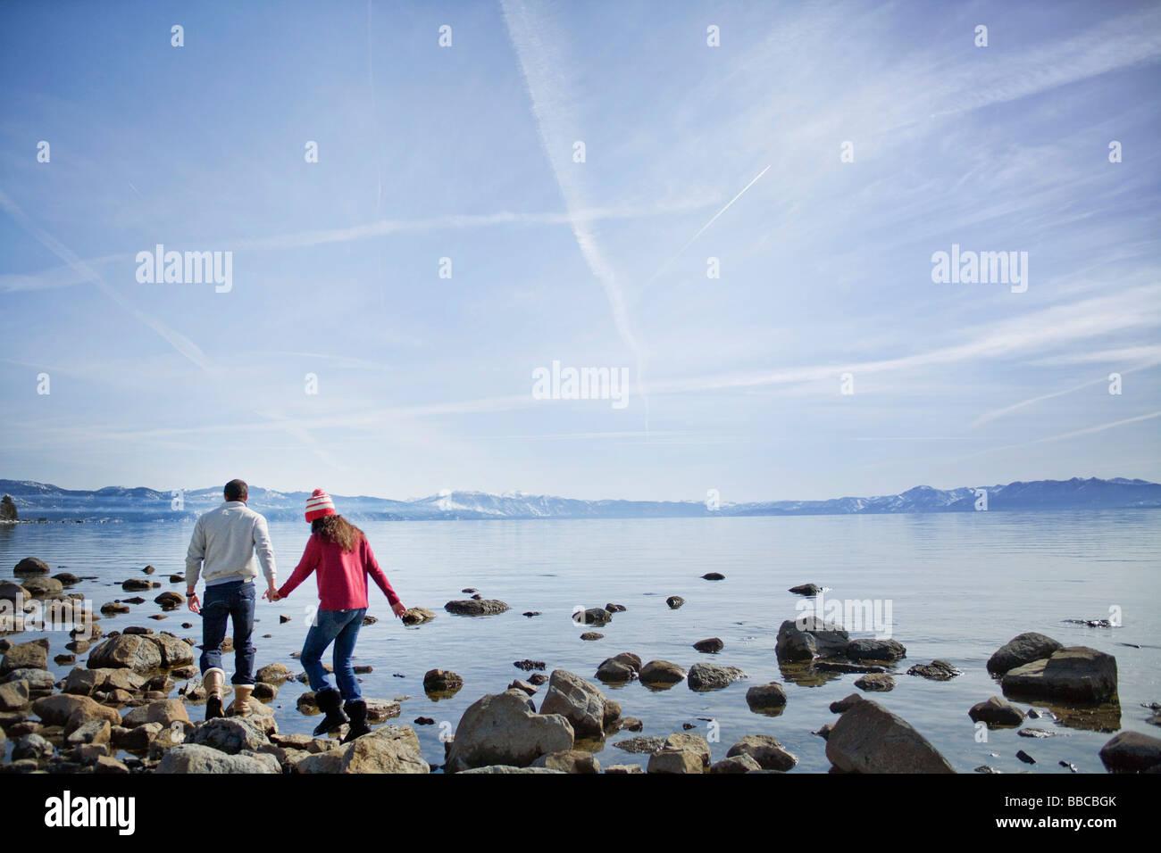 Couple walking on rocks near lake - Stock Image