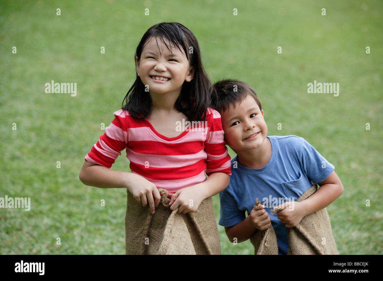 Kids ready for a sack race - Stock Image