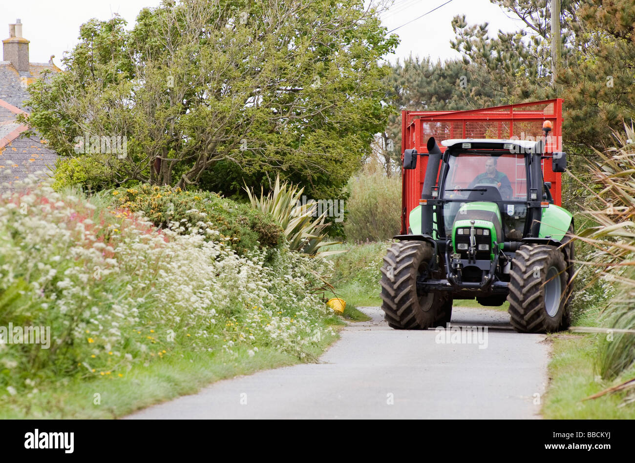 Large green tractor and red cart on a small Cornish lane - Stock Image