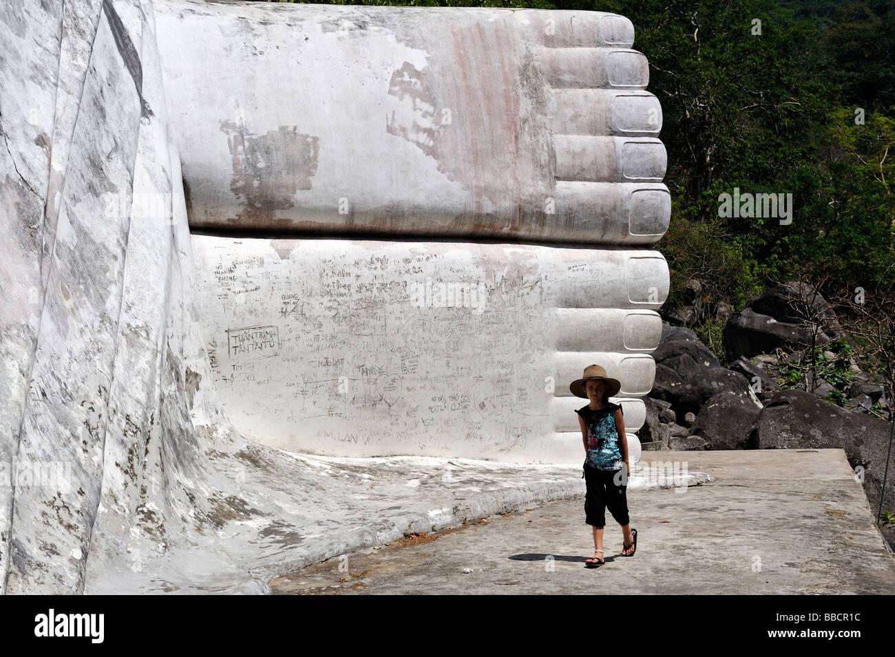 Child near graffiti covered feet of Tuong Phat Nam (white reclining Buddha), Ta Cu mountain, Binh Thuan province, - Stock Image