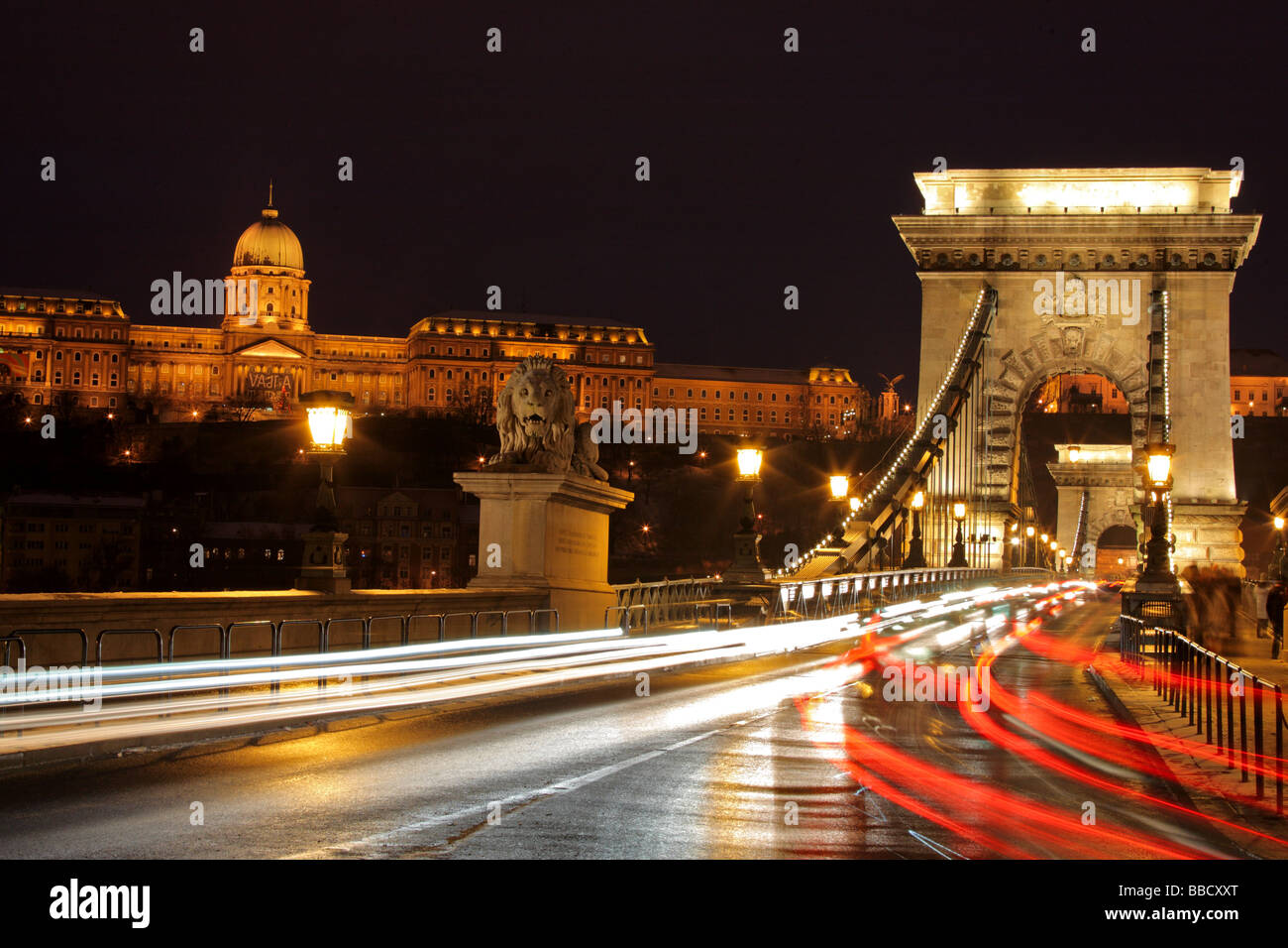 Traffic at the Chain Bridge and the Royal palace of Buda in Budapest, Hungary by night - Stock Image