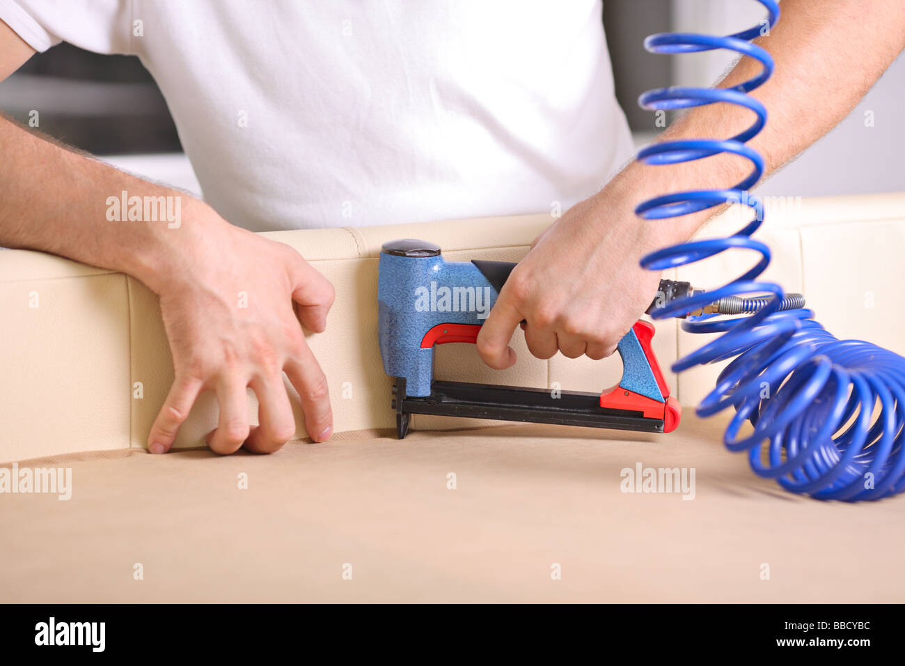 Man using a power tool in a factory - Stock Image
