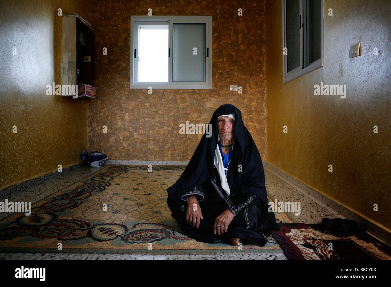 An elderly Bedouin woman sits in the living room of a house in the Bedouin town of Rahat. Negev desert, Israel. - Stock Image