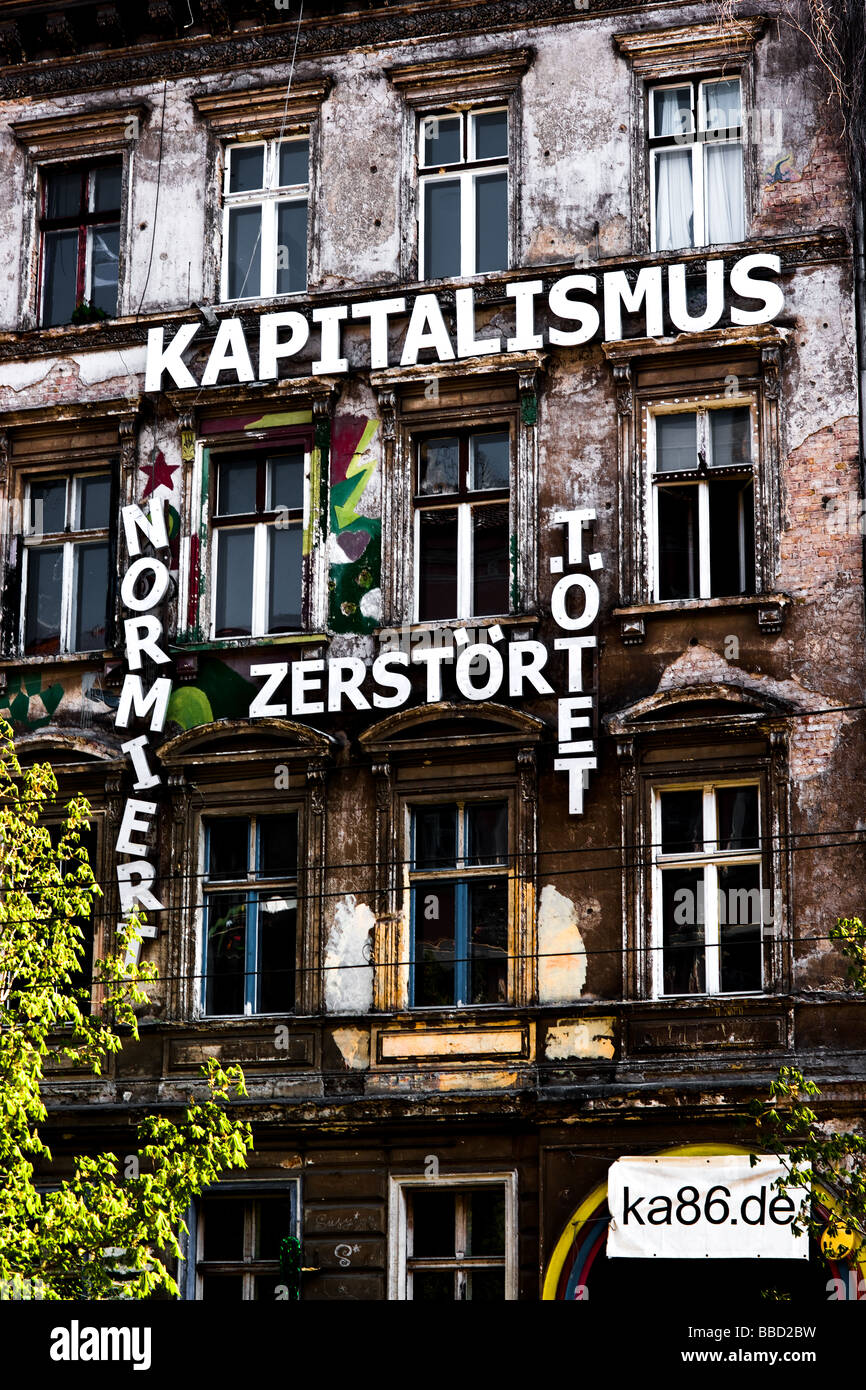 A facade covered with anti capitalist messages at the occupied building at Kastanienallee 86 in Berlin - Stock Image
