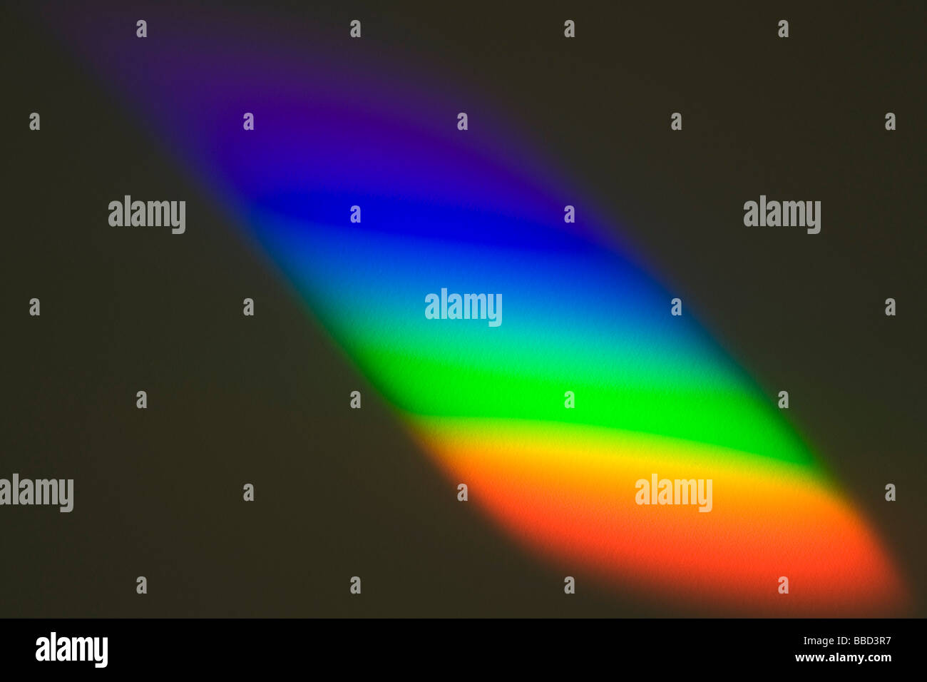 Spectrum cast by a prism from sunlight through a window on to white paper - Stock Image