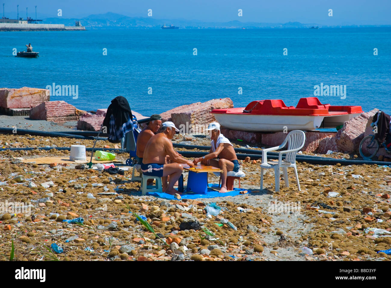 People playing a boardgame on a dirty beach in Durres Albania Europe - Stock Image