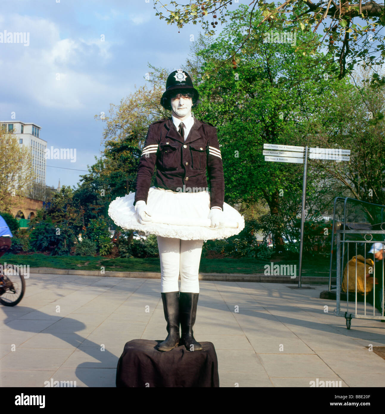 A London Southbank comic mime street policeman performer wearing a Metropolitan Police uniform and a white tutu - Stock Image