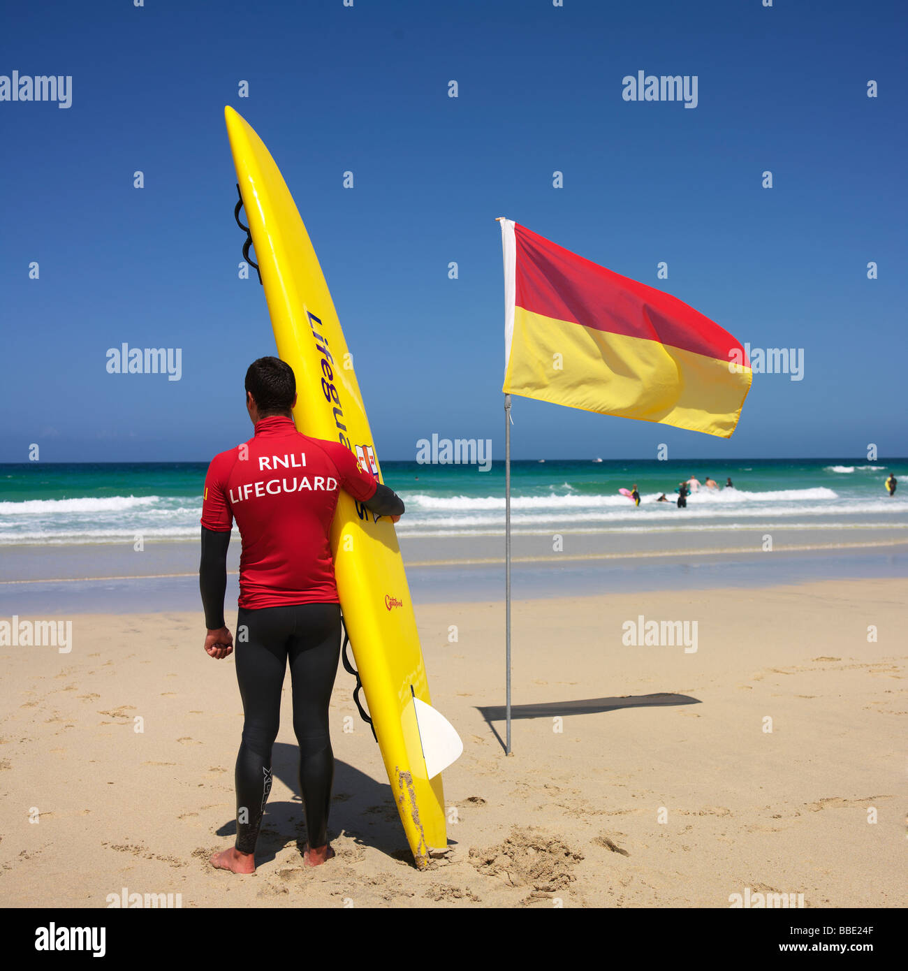 Lifeguard looking out to see, holding a rescue surfboard - Stock Image