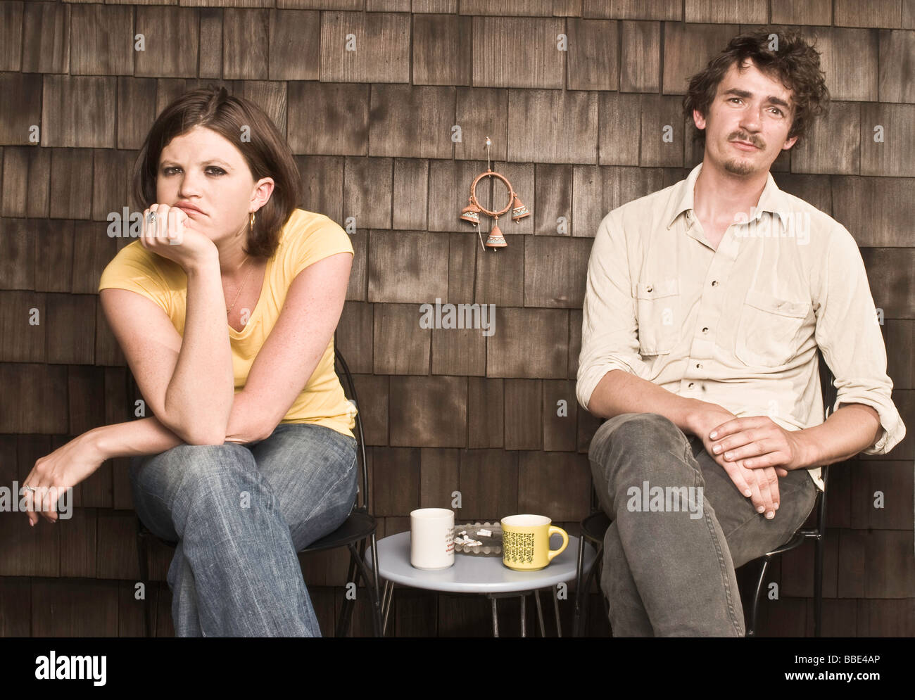 A young woman and a young man are sitting on chairs, looking disconnected from each other, with a coffee table in - Stock Image