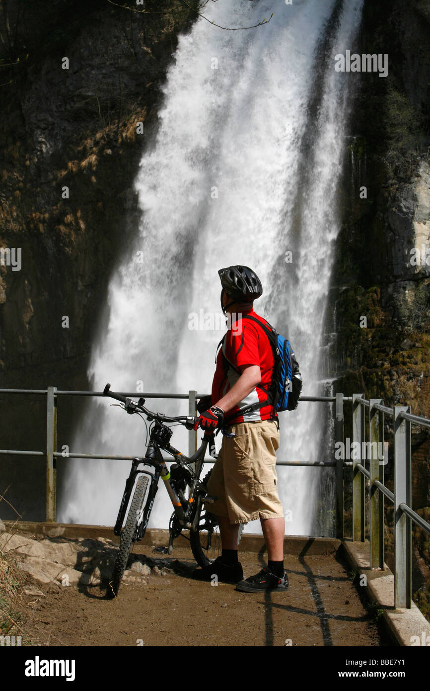 Biker marvels at the thundering waterfalls of Rinquelle, Rin Spring, and Seerenbach, Betlis, St. Gallen, Switzerland, Stock Photo