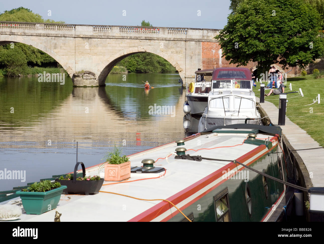 A canoe approaching boats moored on the river Thames at Shillingford, Oxfordshire, UK - Stock Image