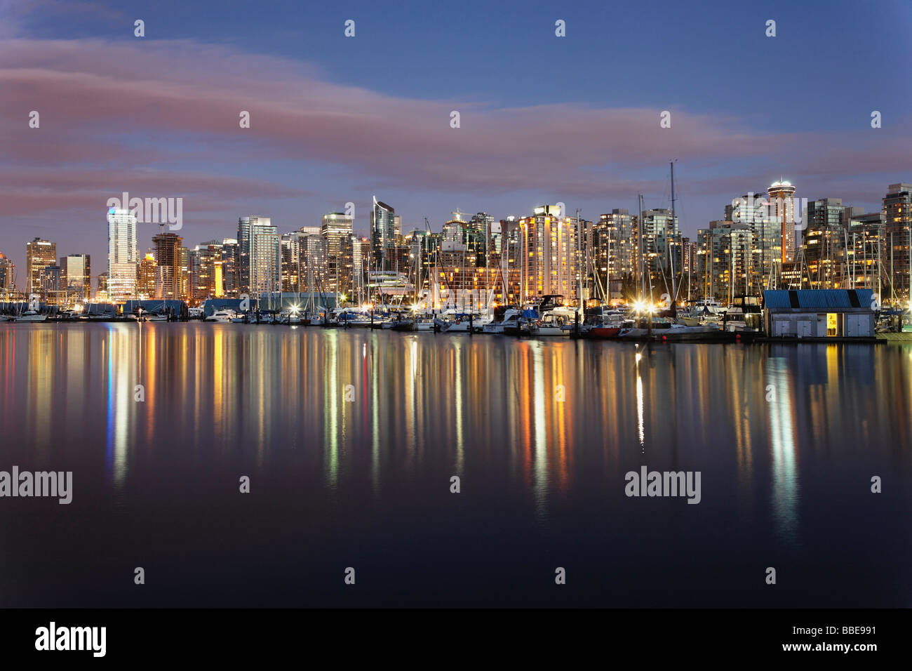 Vancouver skyline and boat harbour reflect in the waters of Coal Harbour - Stock Image