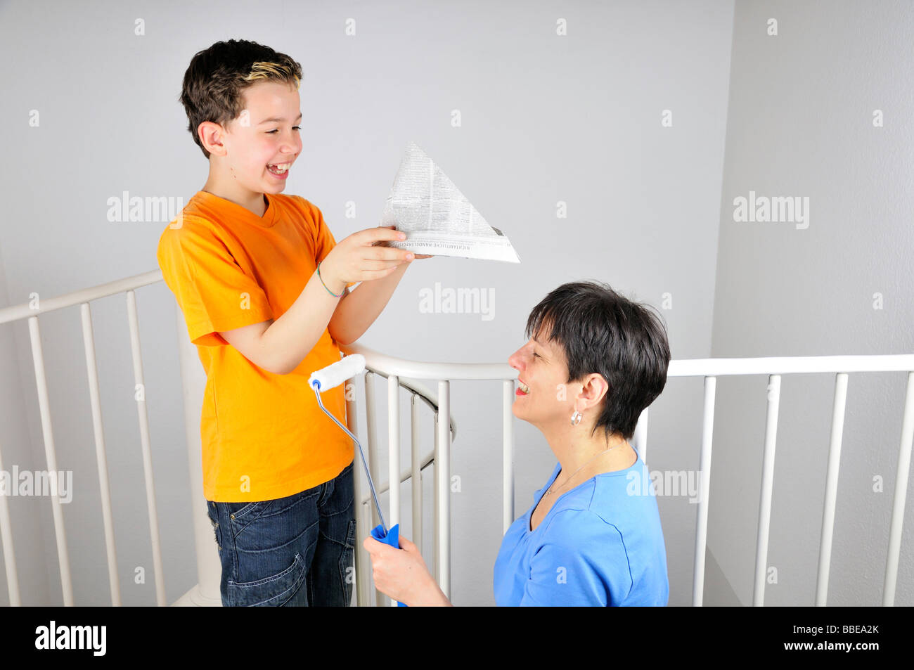 Paintwork, boy putting a paper hat on his mother's head - Stock Image