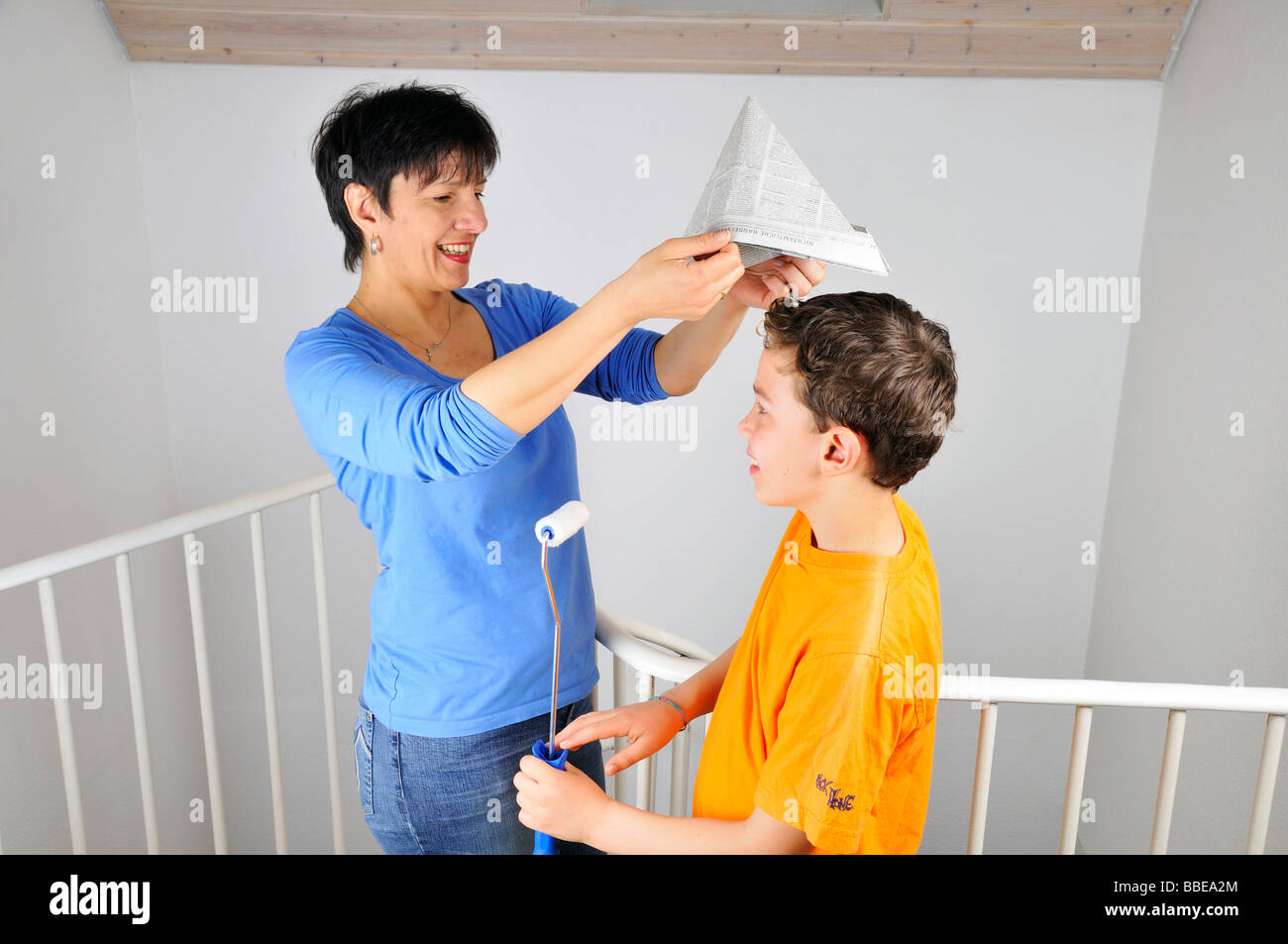Paintwork, woman putting a paper hat on her son's head - Stock Image
