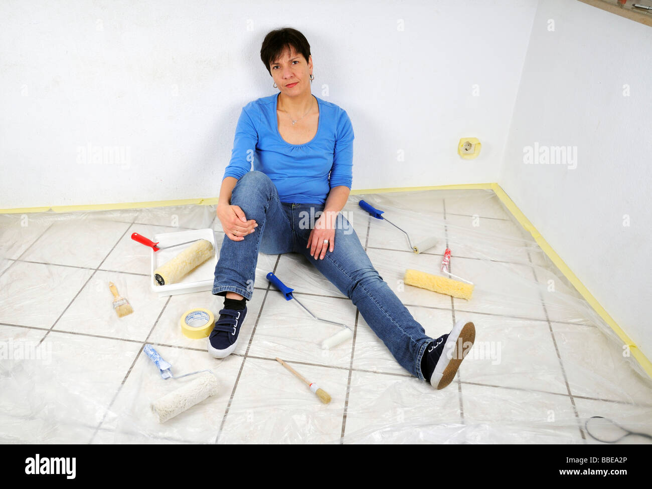 Paintwork, annoyed woman in the midst of painting utensils - Stock Image