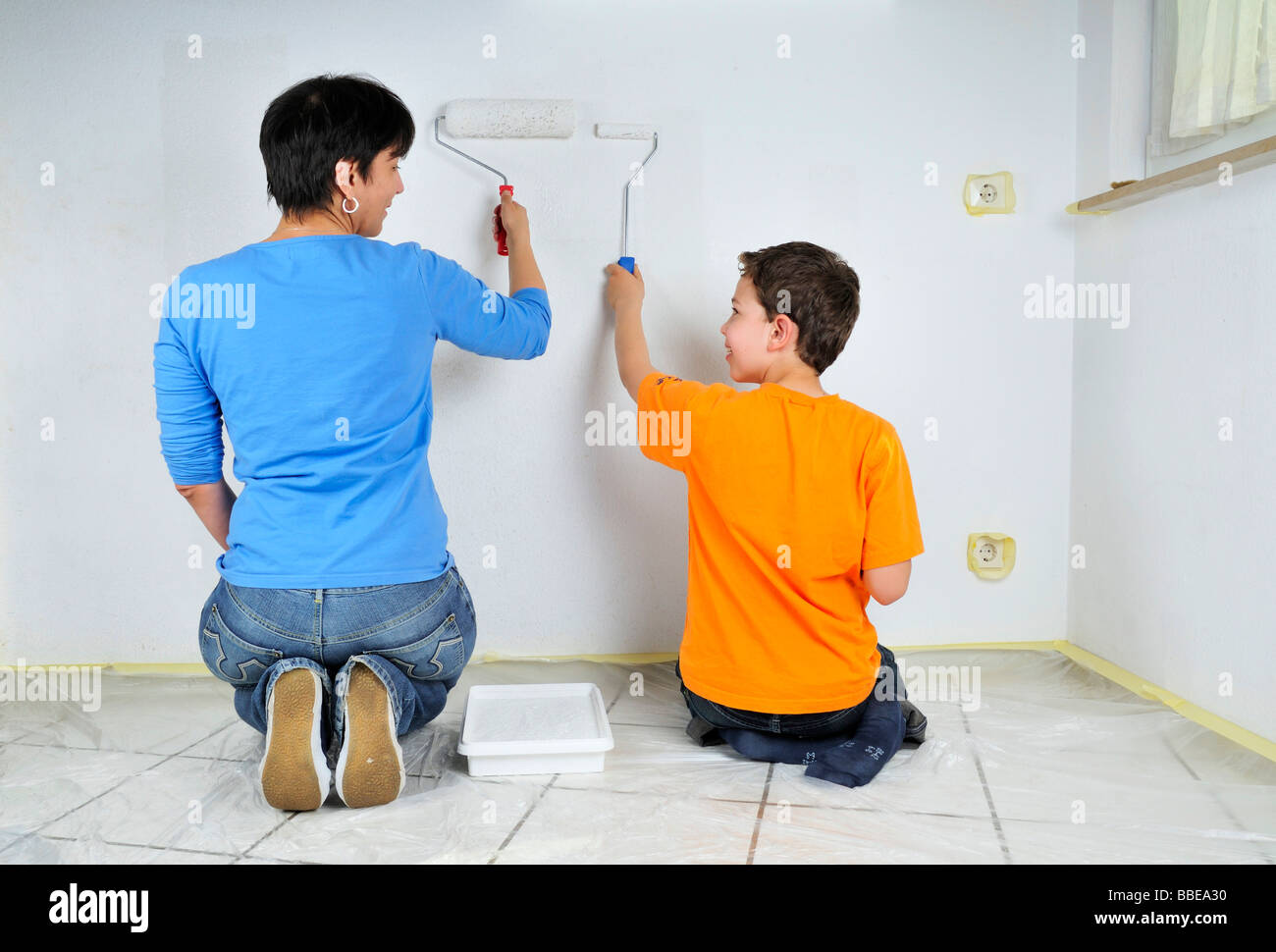 Paintwork, mother and son painting wall with paint rollers - Stock Image