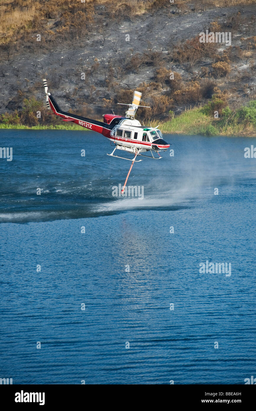 FIre fighting helicopter takes on water from Lauro Reservoir during Jesusita Fire, Santa Barbara, California, May - Stock Image