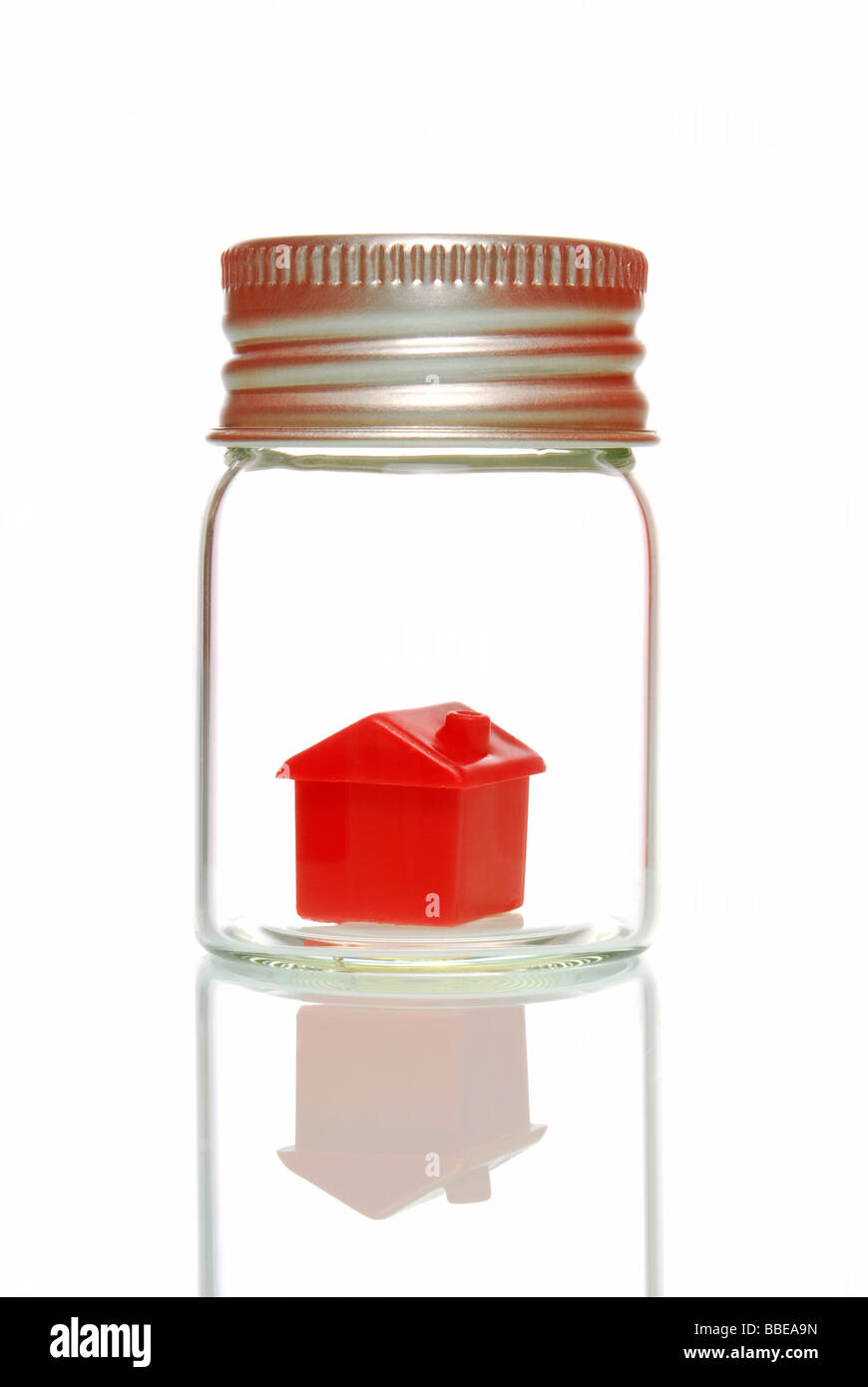 Miniature house in glass, symbolic for being protected, insurance - Stock Image