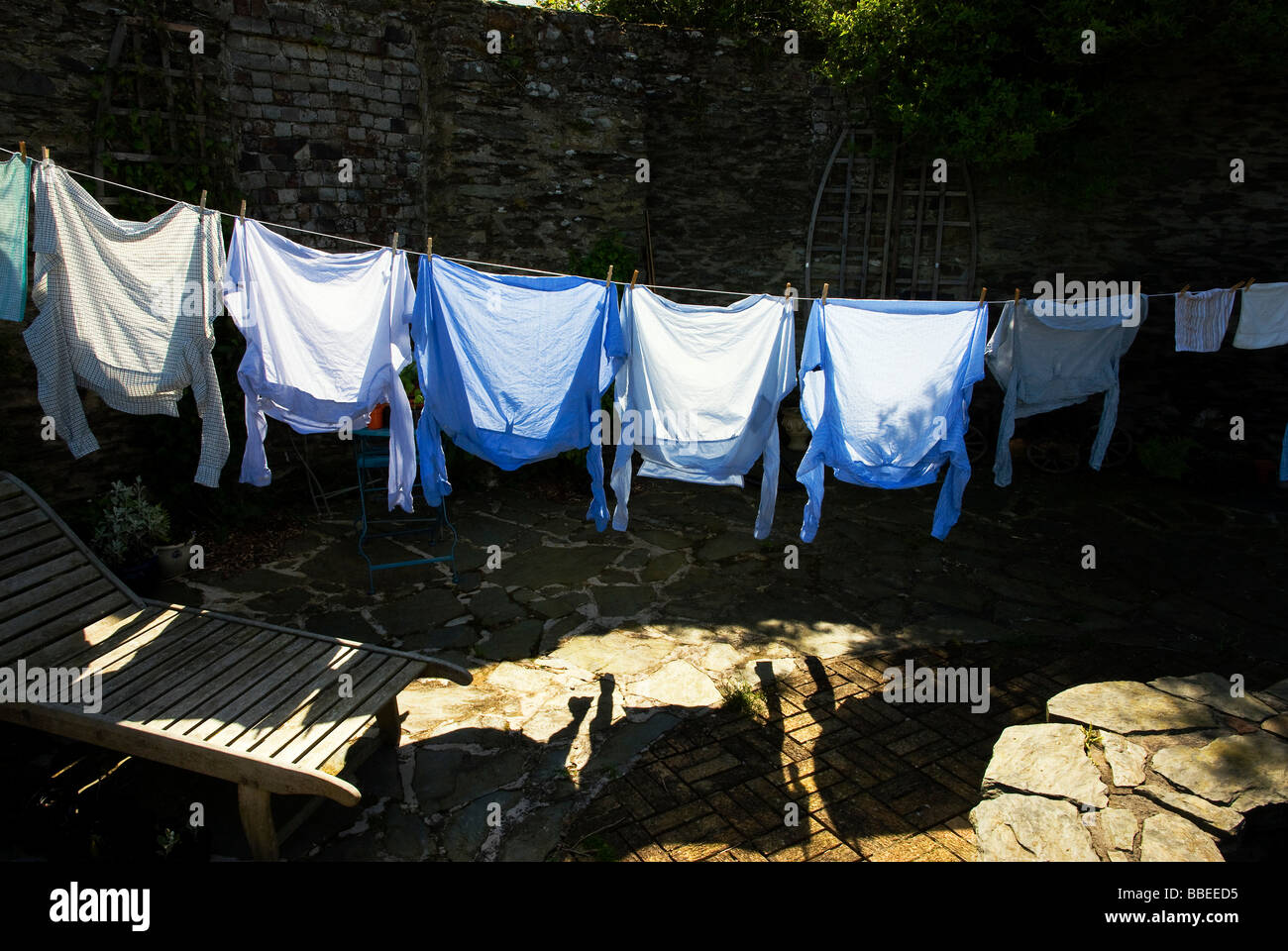 Mens shirts on a traditional washing line in sunlight - Stock Image