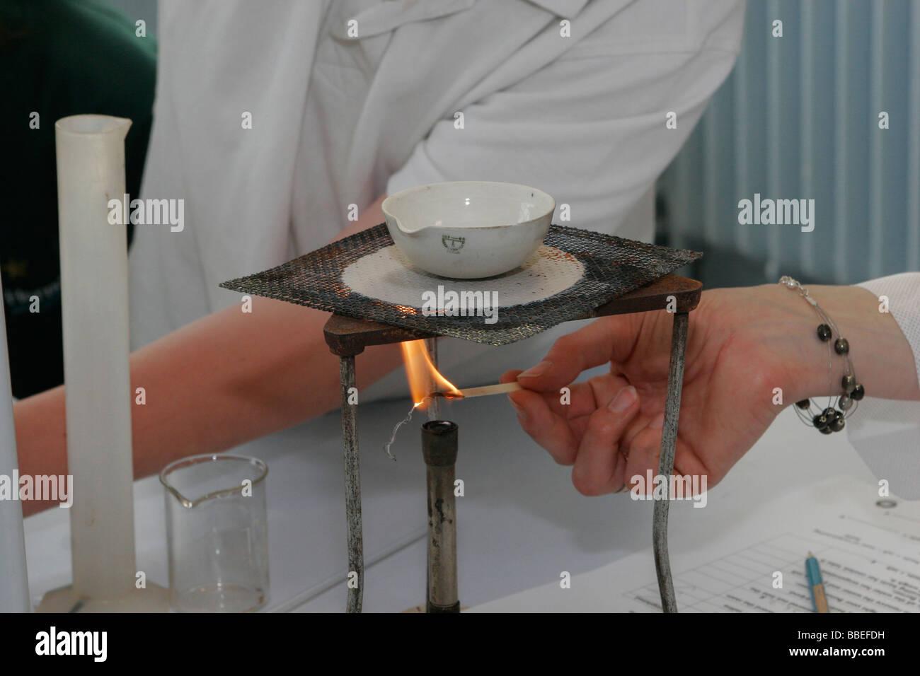 CHILDREN Education Secondary School Teacher lighting Bunsen burner used for food technology experiment measuring - Stock Image