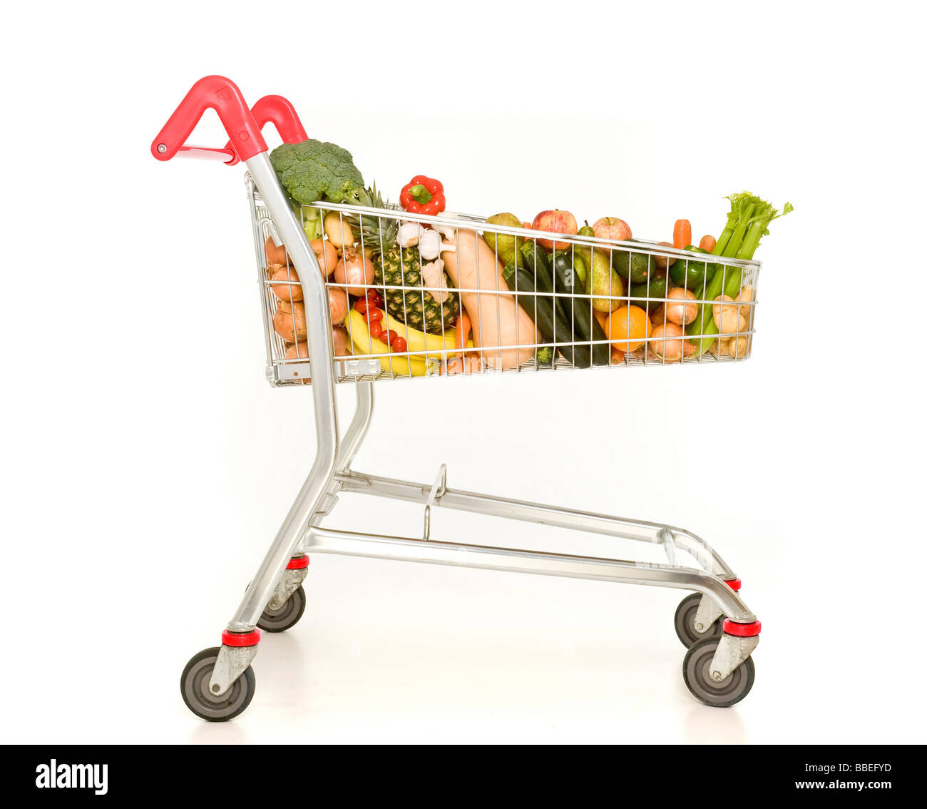 Supermarket shopping trolley filled with fruit and vegetables on white background - Stock Image
