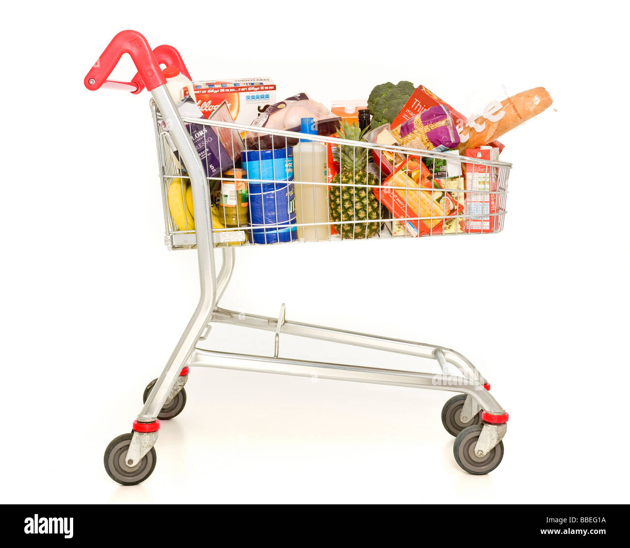 Supermarket shopping trolley filled with weekly shopping on white background - Stock Image