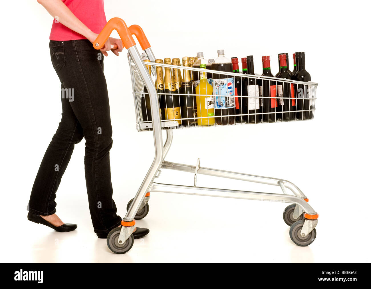 casually dressed female pushing supermarket trolley filled with bottles of wine and champage - Stock Image
