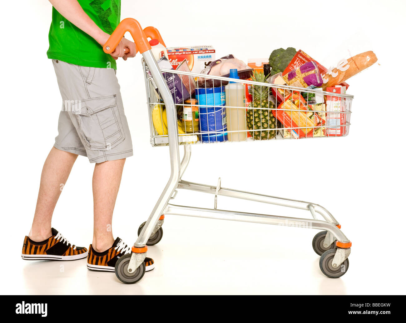 Casually dressed male pushing supermarket shopping trolley filled with weekly shopping on white background - Stock Image