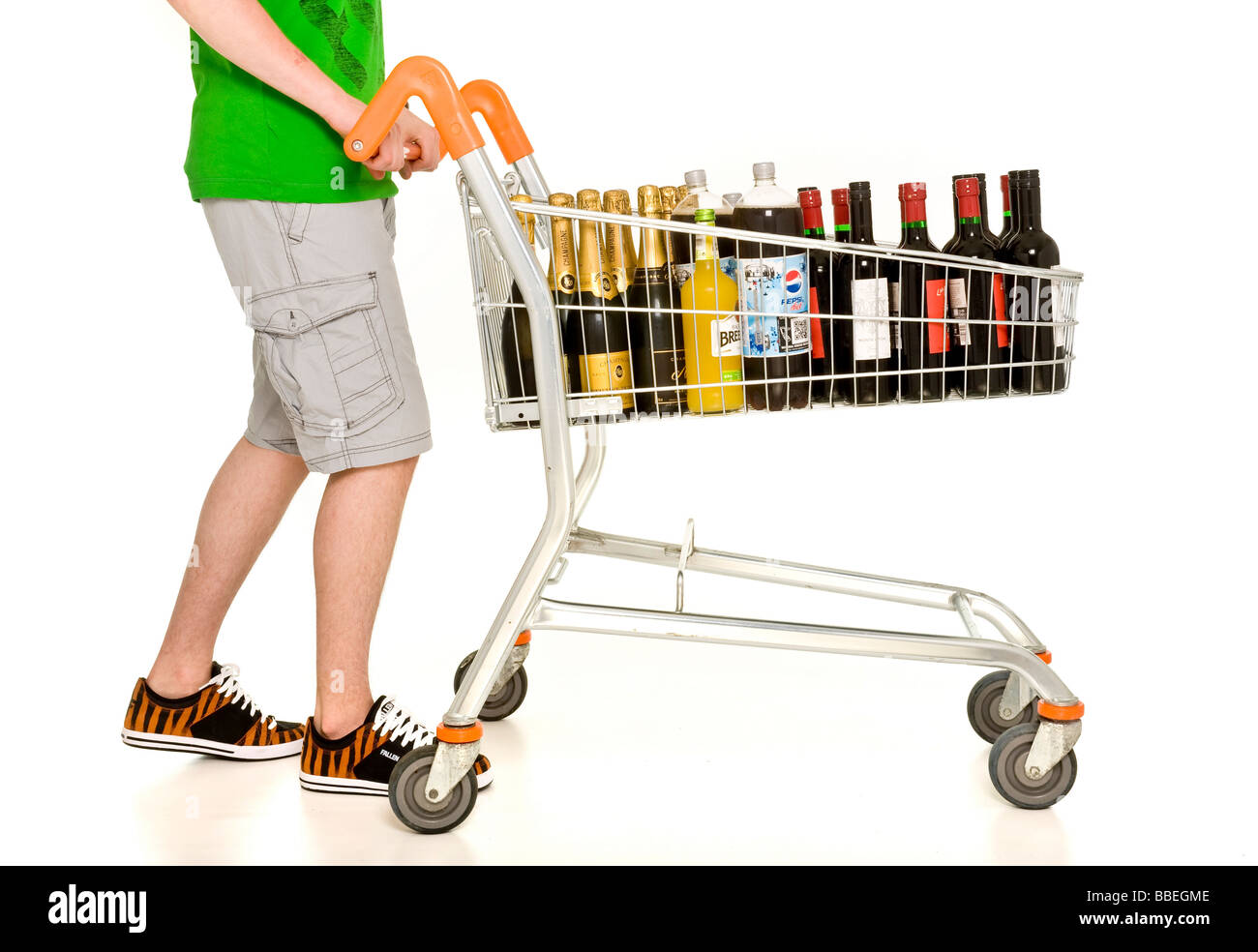 Casually dressed male pushing supermarket shopping trolley filled bottle of wine and champagne - Stock Image