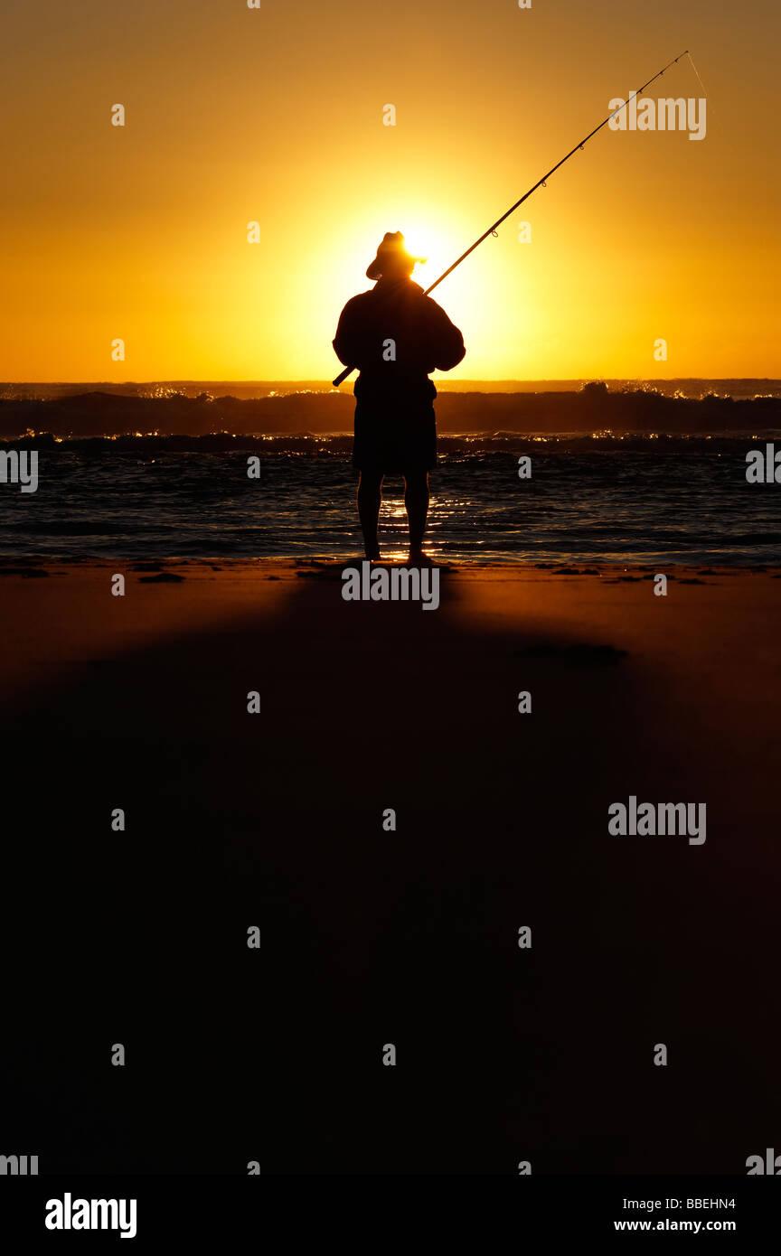 Fisherman on beach at sunrise - Stock Image