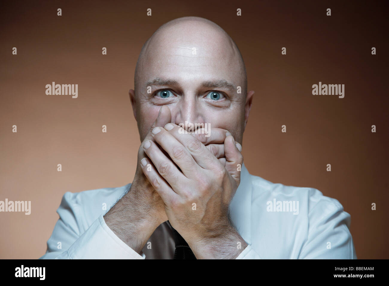 Portrait of Man Covering Mouth with Hands Stock Photo