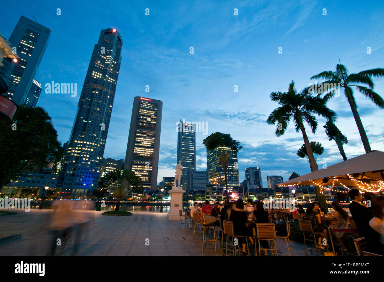 Skyline of Singapore  Raffles Statue street cafe South East Asia twilight SingapurStock Photo