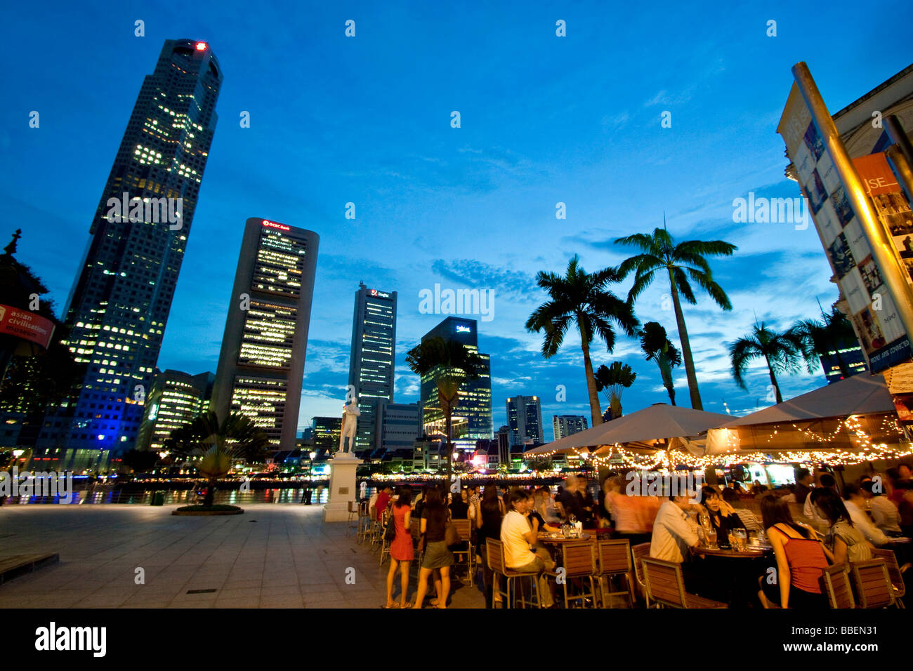 Skyline of Singapores Raffles Statue street cafe South East Asia twilight Stock Photo