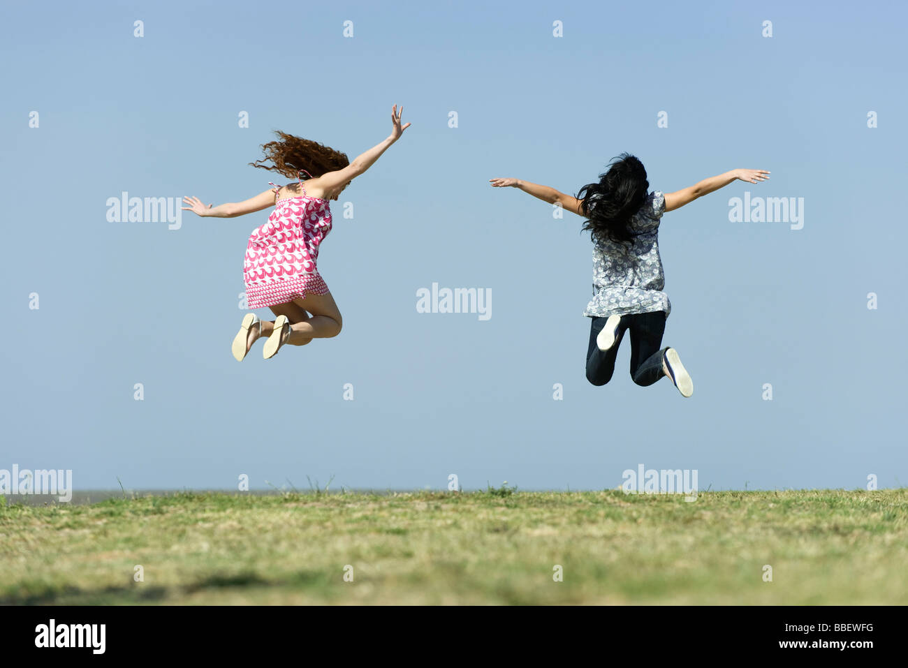 Two young women jumping in midair outdoors, rear view - Stock Image