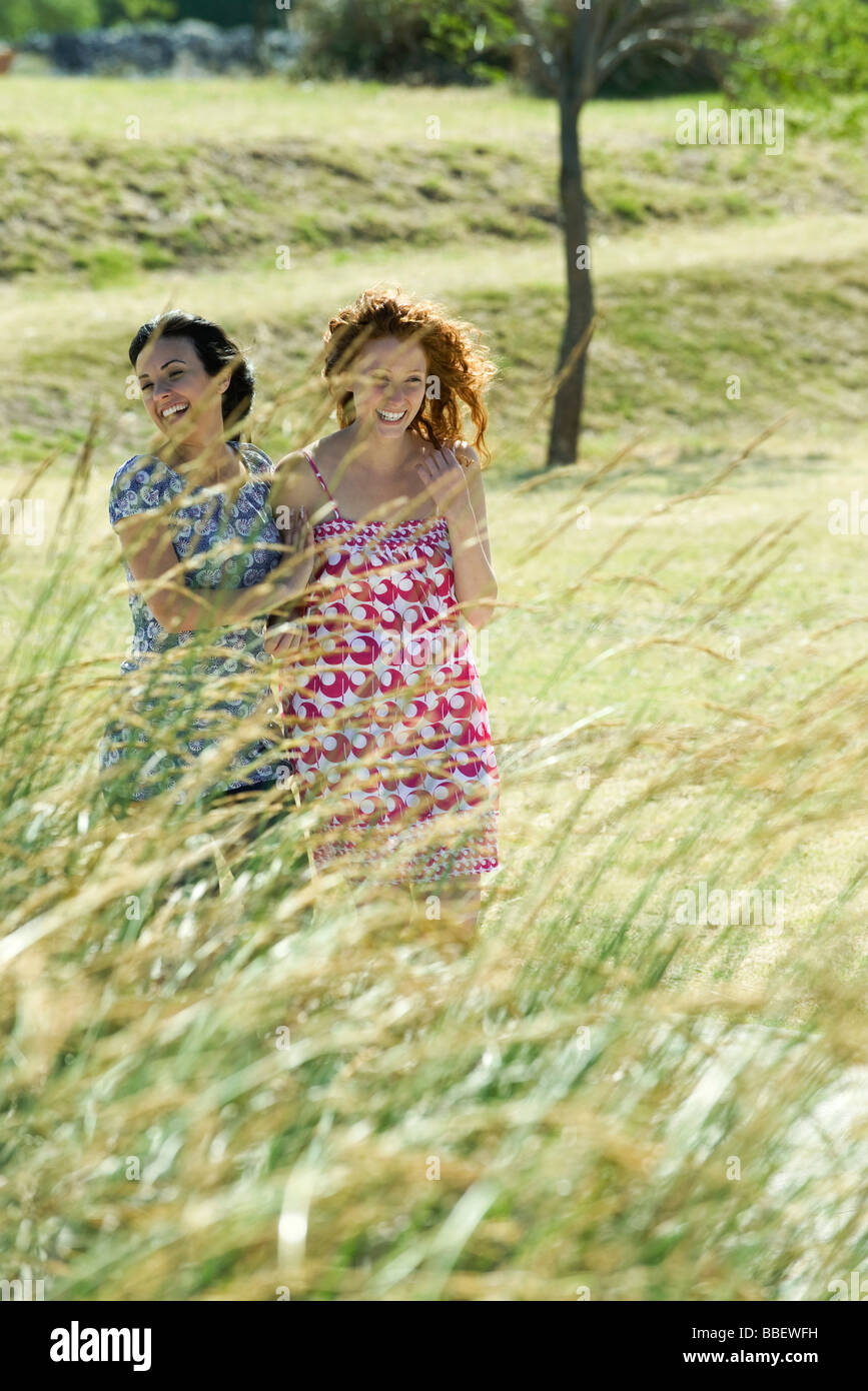 Two young women laughing together outdoors, tall grass in foreground - Stock Image