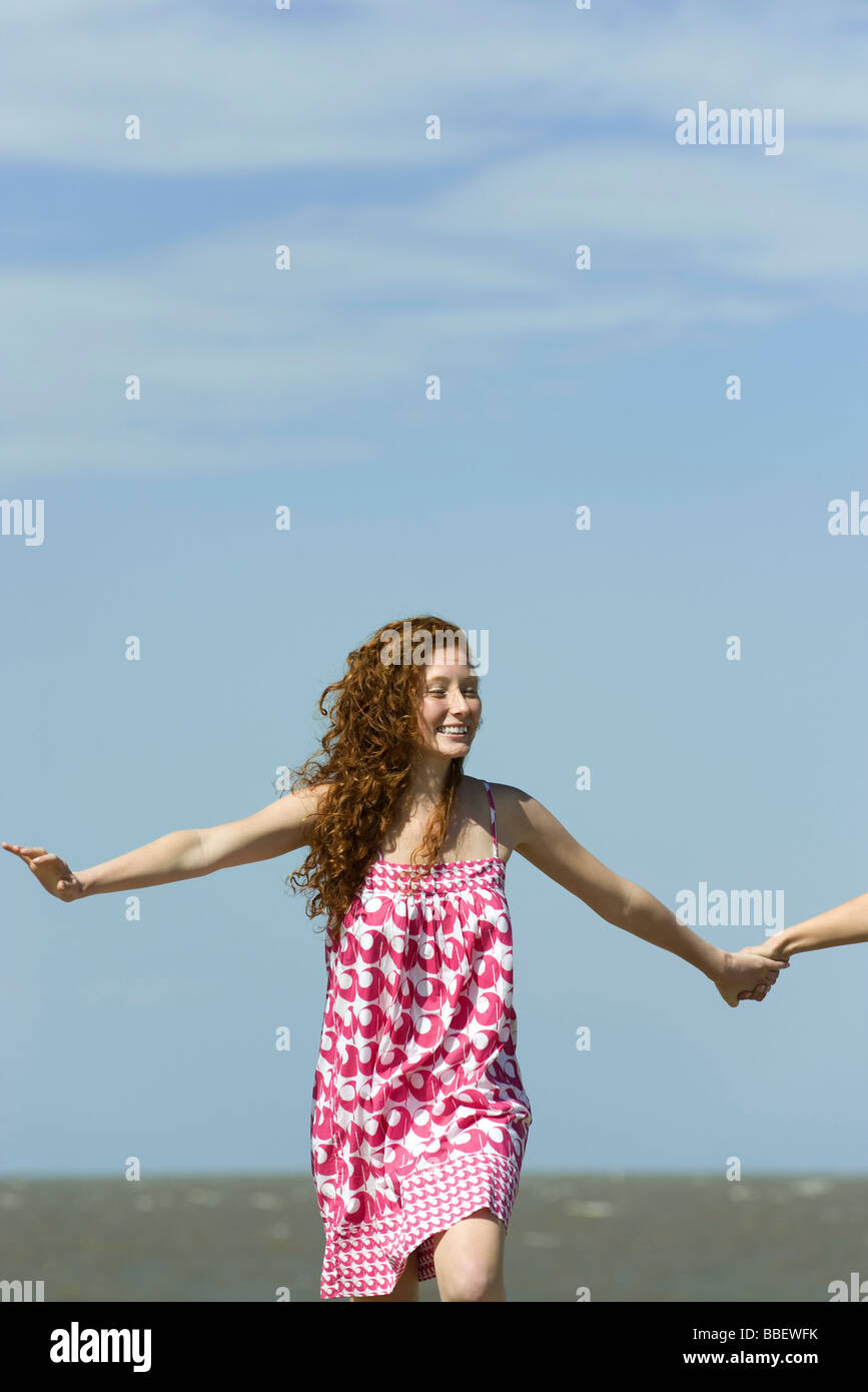 Young woman running with arms out, holding friend's hand, cropped - Stock Image