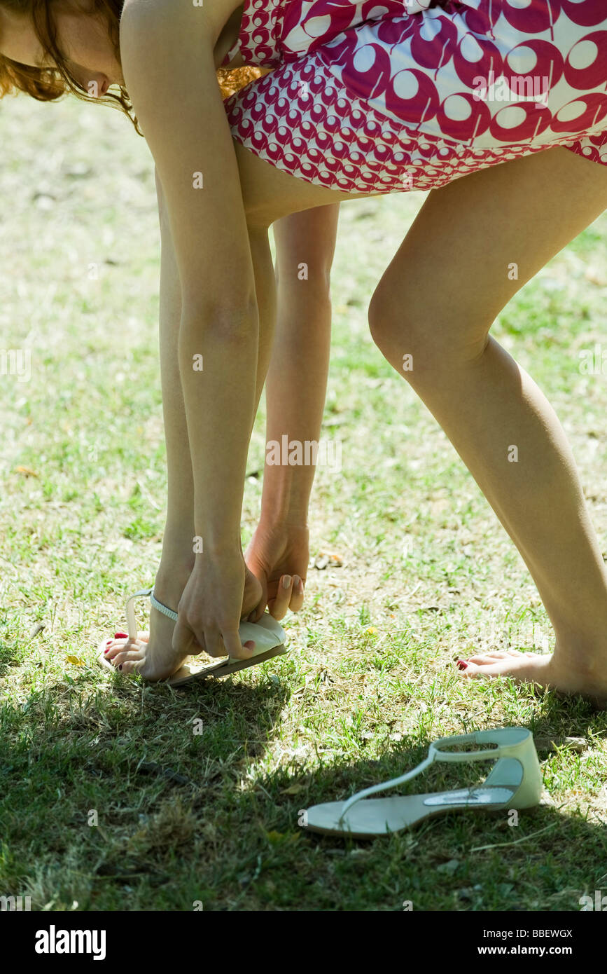 Young woman bending over to put on sandal, cropped - Stock Image