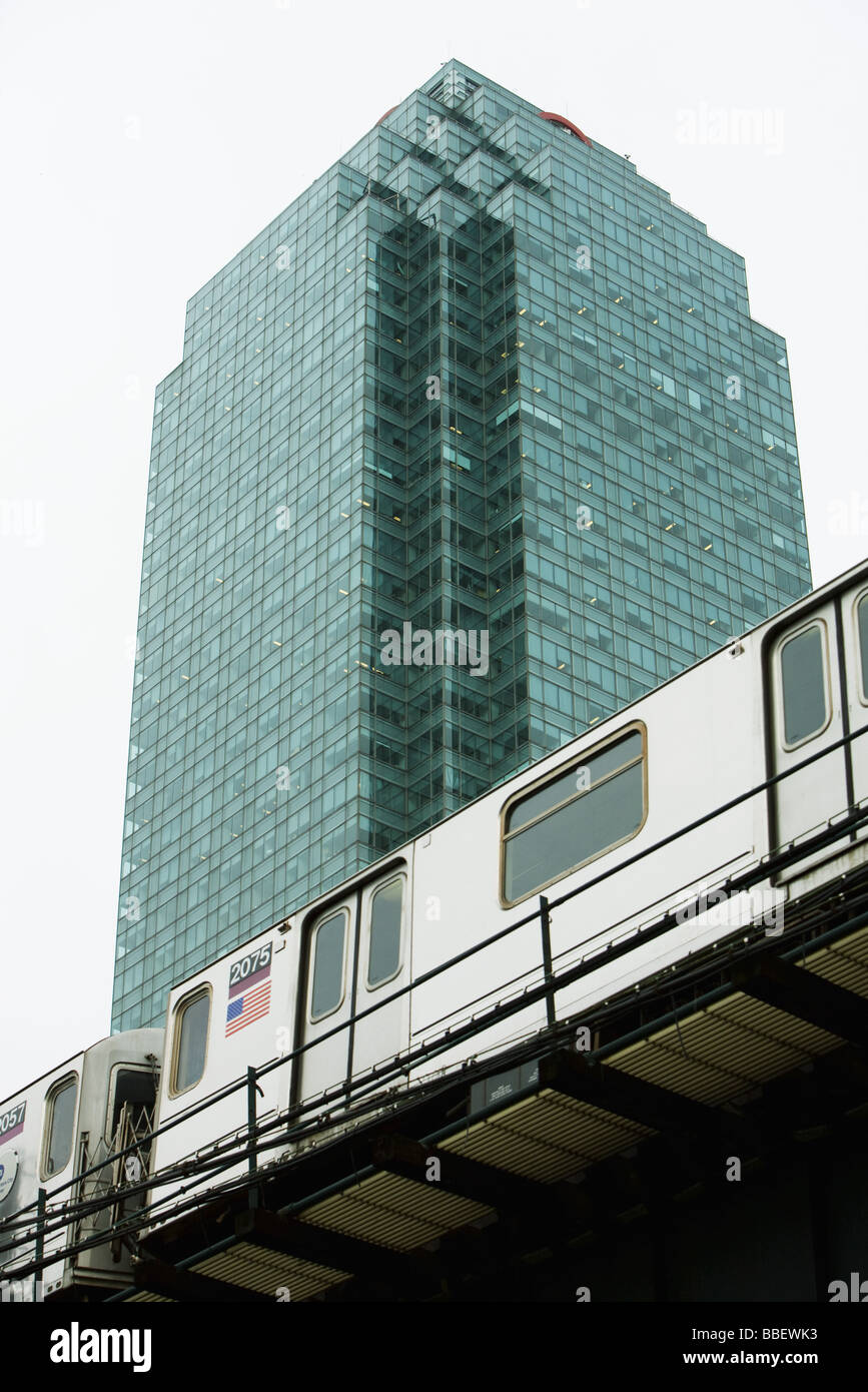 Elevated subway, office building in background, low angle view - Stock Image