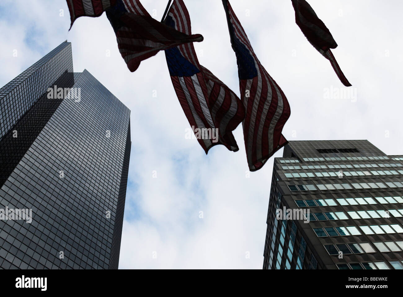 Skyscrapers, flags waiving in breeze, viewed from below - Stock Image