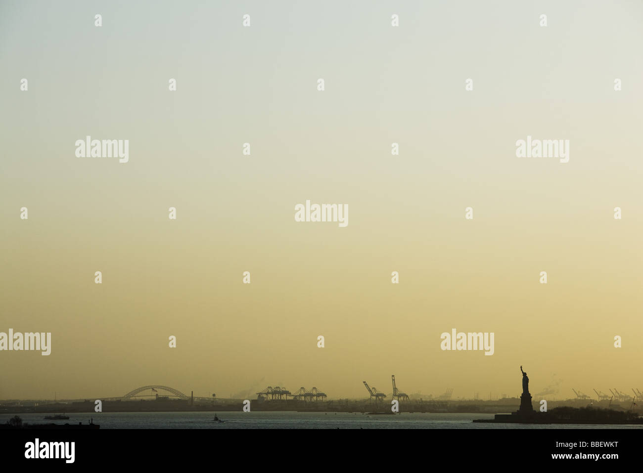 United States, New York City, New York Harbor at sunrise, Statue of Liberty visible in distance Stock Photo
