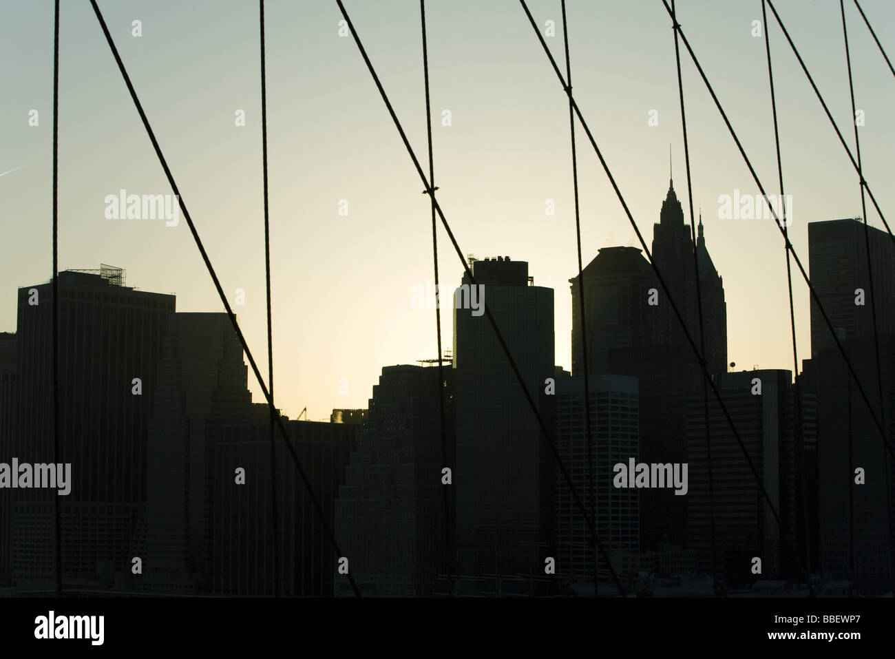 United States, New York City, silhouette of Manhattan skyline seen through Brooklyn Bridge - Stock Image