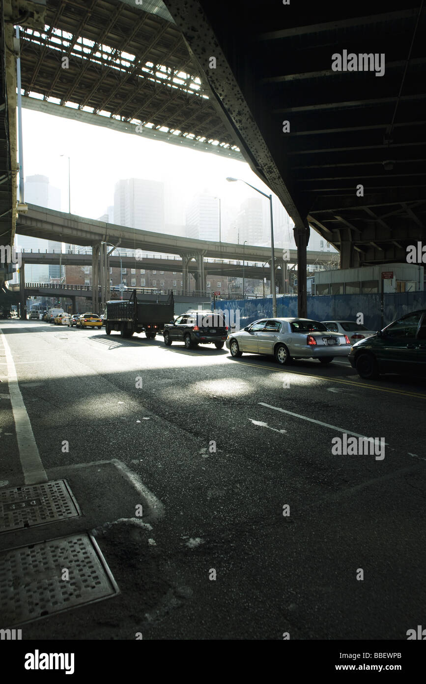 Traffic waiting at traffic signal on street beneath elevated road - Stock Image